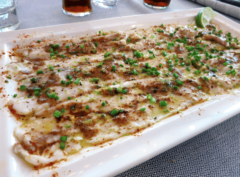 Le bar en carpaccio servi tiède avec graines de moutarde et citron vert